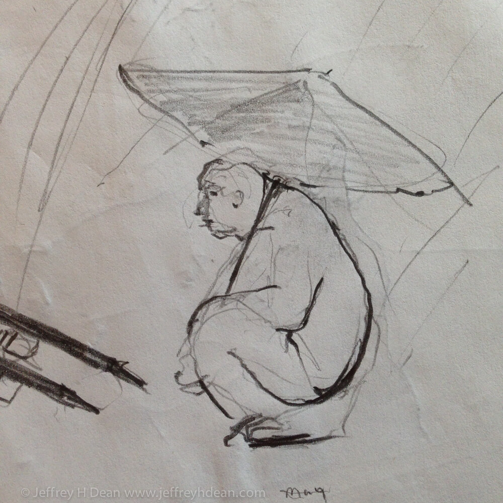 A man squats under his umbrella beside is vendiing cart.