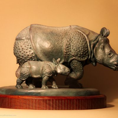 Bronze sculpture of a mother Indian rhino walking with her baby.