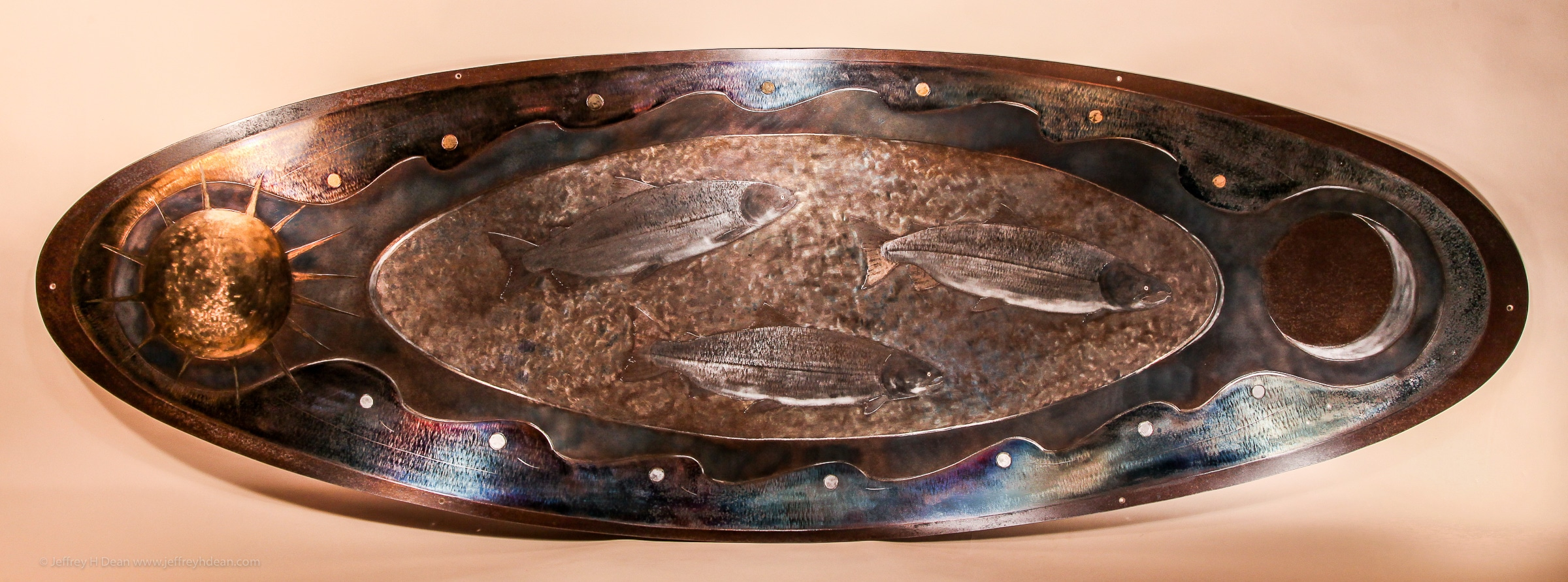 Salmon metal wall art. Three silver salmon swim between the tides, the sun and moon in this engraved and heat tinted steel metal wall art.