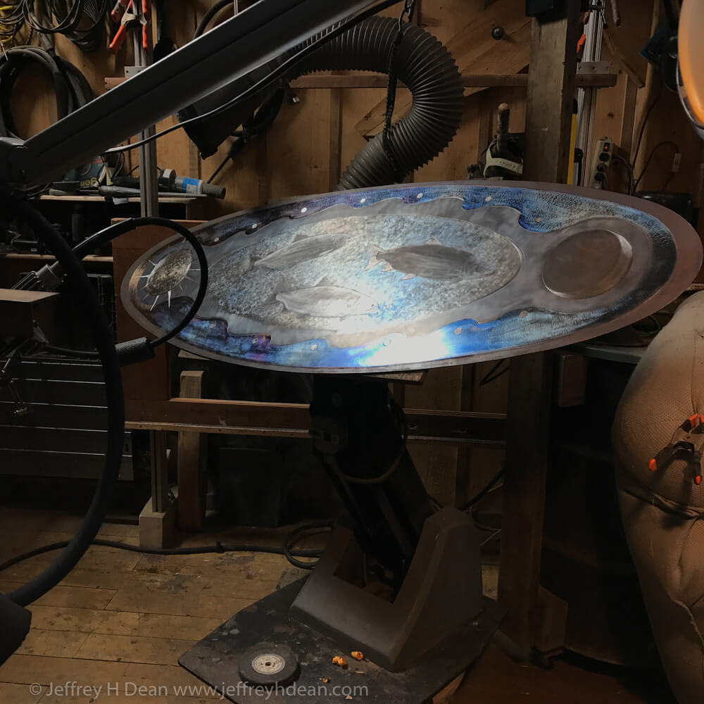 The sky has been ground and colored. You can see the old dental chair stand I use for a work station. It has a tilting rotary table mounted on it. The work is held to the table with on/off magnets.