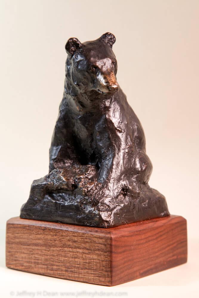 Bronze sketch of seated black bear.
