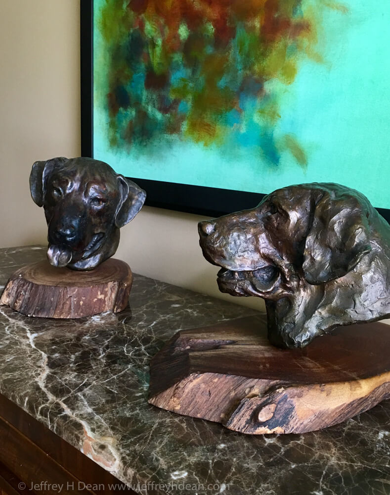 Two bronze dog portraits on marble shelf.