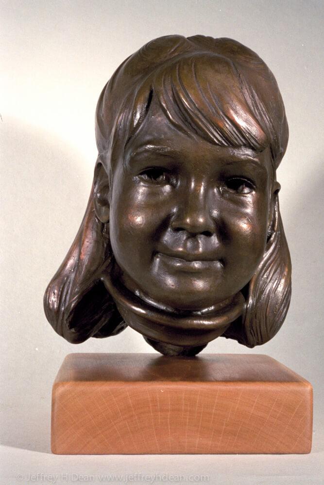 A bronze portrait sculpture of a young girl.