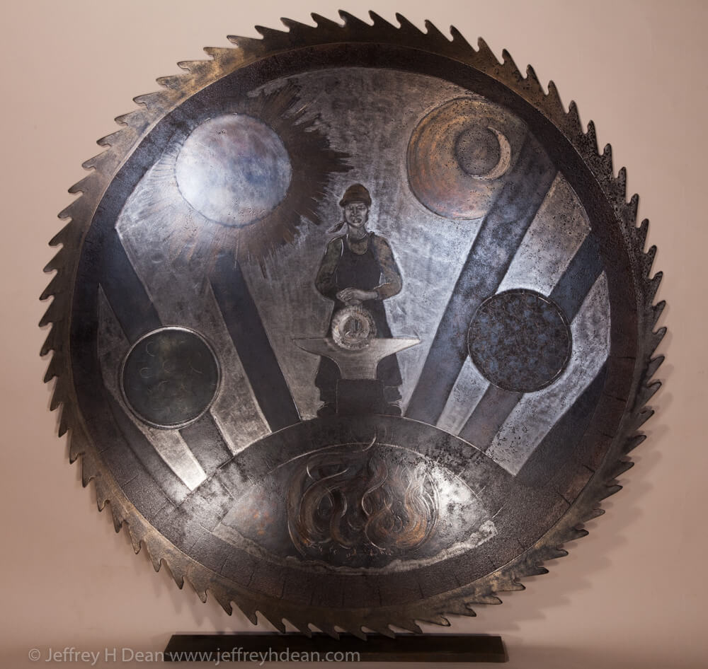 Earth, air, fire and water; the resources of the smith. Engraved steel saw blade metal wall art of blacksmith in the forge.