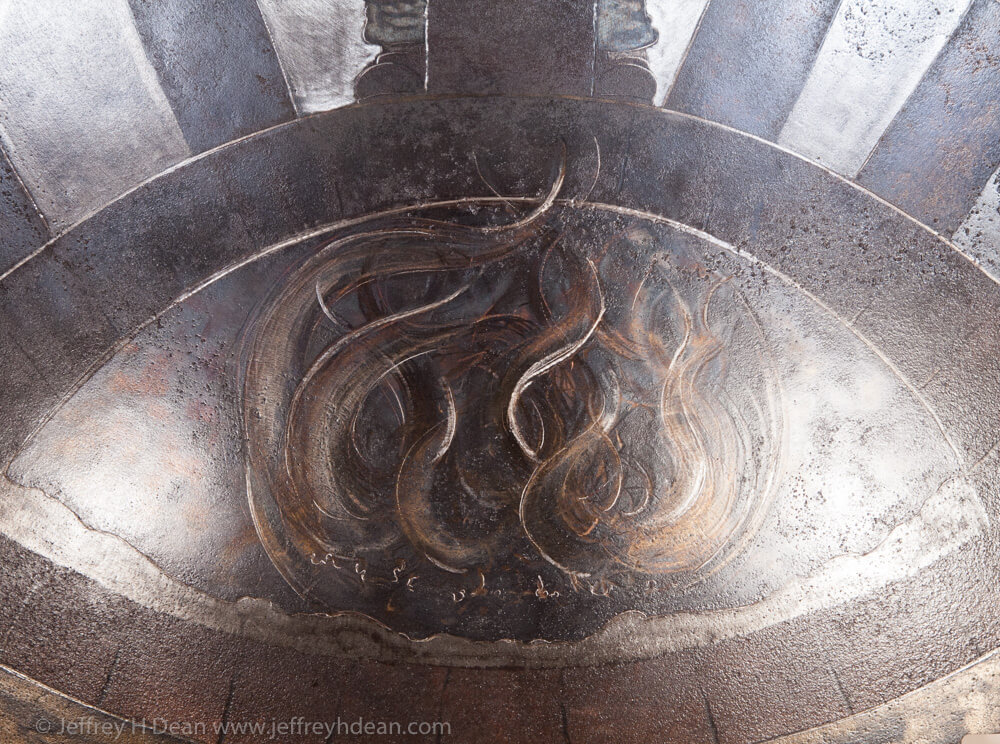 Earth, air, fire and water; the resources of the smith. Engraved steel sawblade of blacksmith in the forge.
