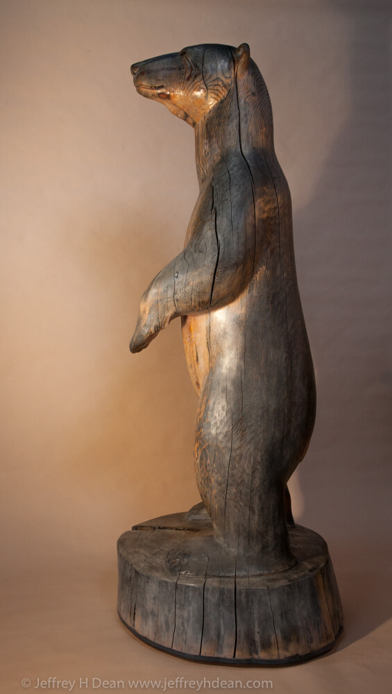 White spruce carving of polar bear in the rays of the first arctic sun.