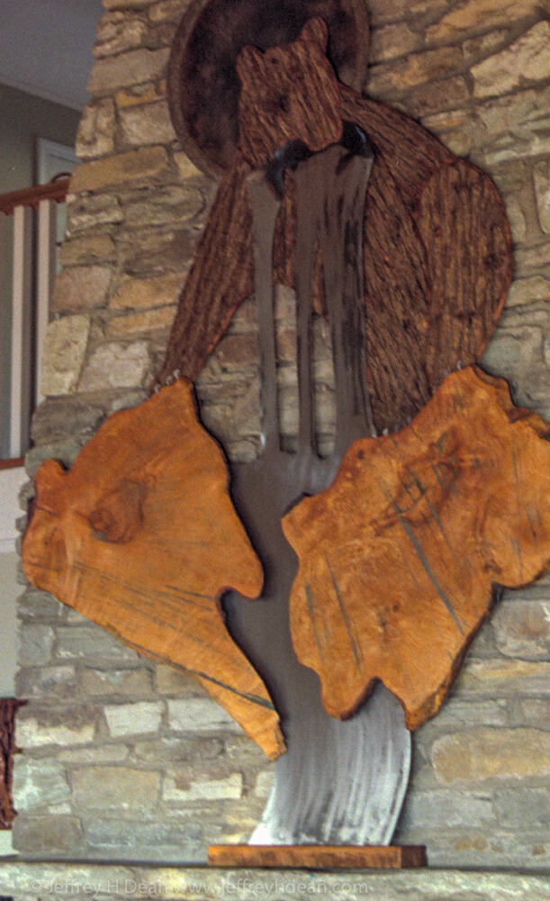 Large chimney relief of fishing bear with the sun shining from behind. Maple, heat tinted steel and wormy chestnut bark.