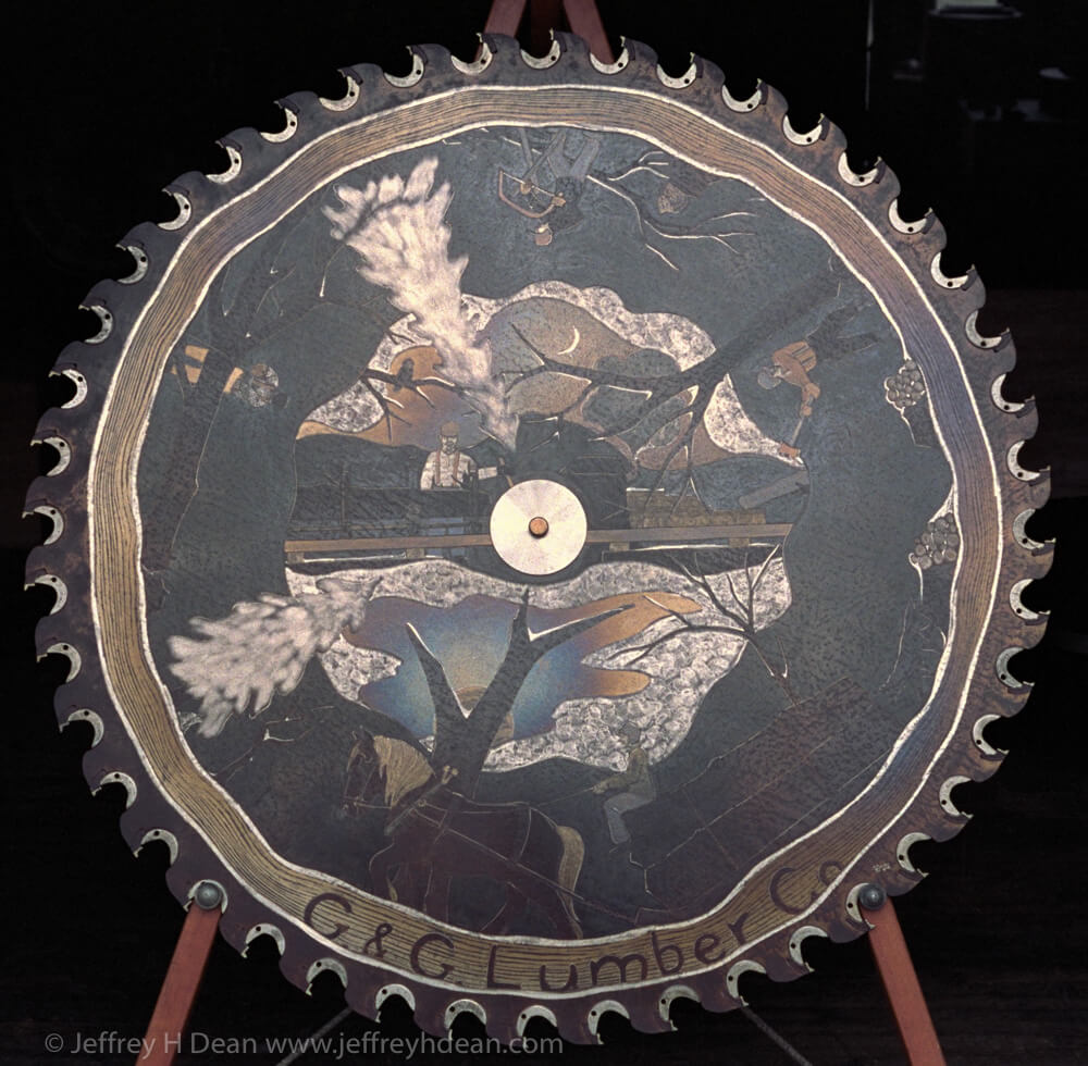 G and G Lumber sawmill scene. Engraved steel  saw blade metal wall art  with heat tints.