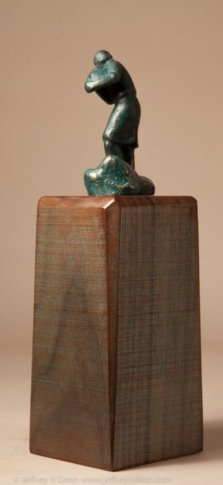Bronze miniature sculpture of man carrying a basket of mountain herbs.