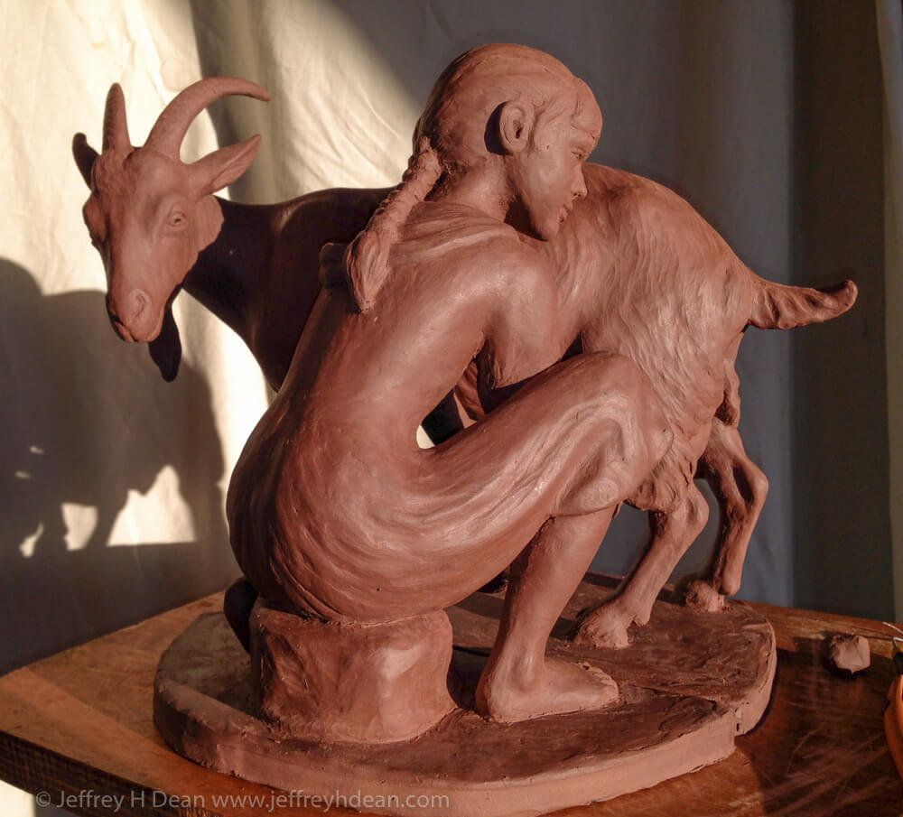 Clay model for bronze sculpture of girl milking goat.