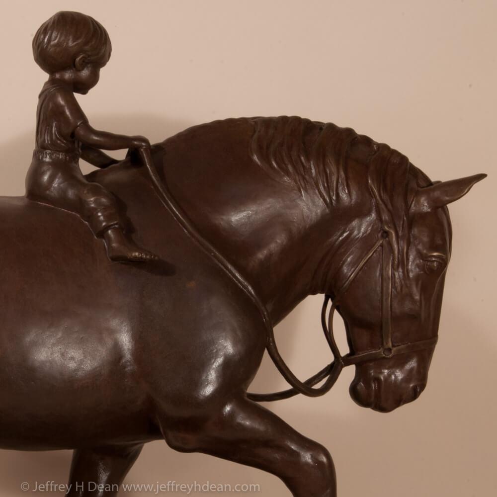 Bronze sculpture of a young boy riding a draft horse.
