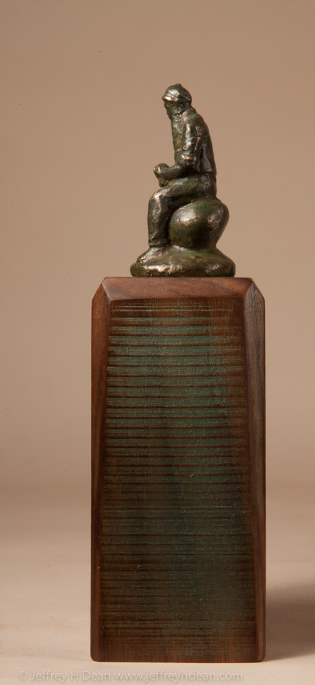 Miniature bronze sculpture of old timer sitting on a rock eating an apple.
