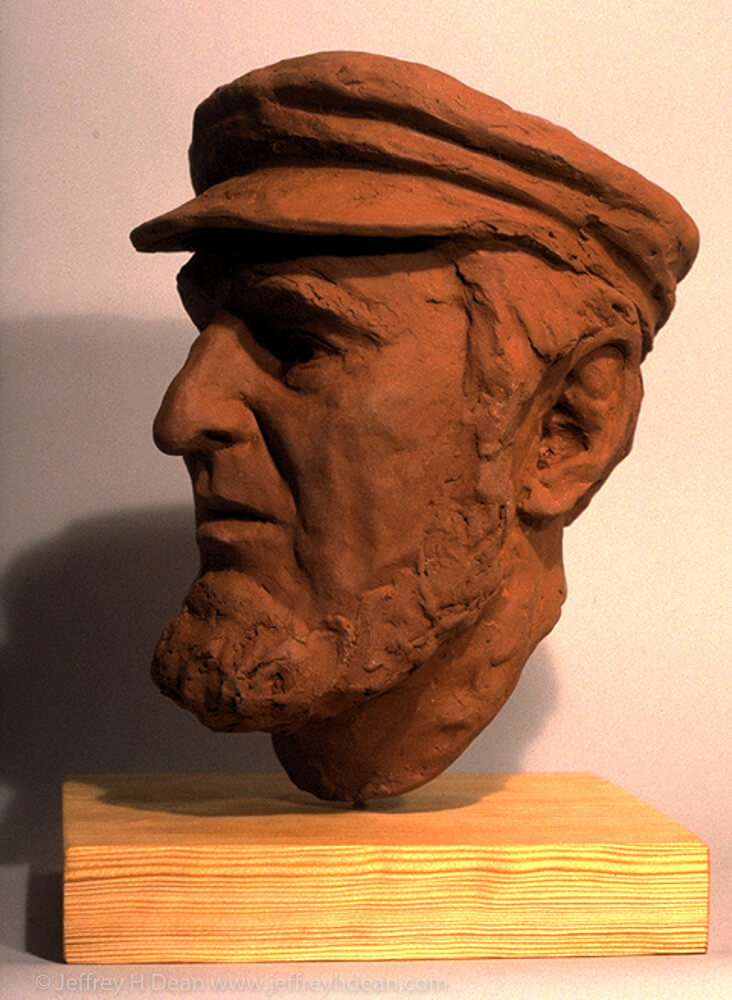 Fired clay portrait sculpture of a man with a cap.