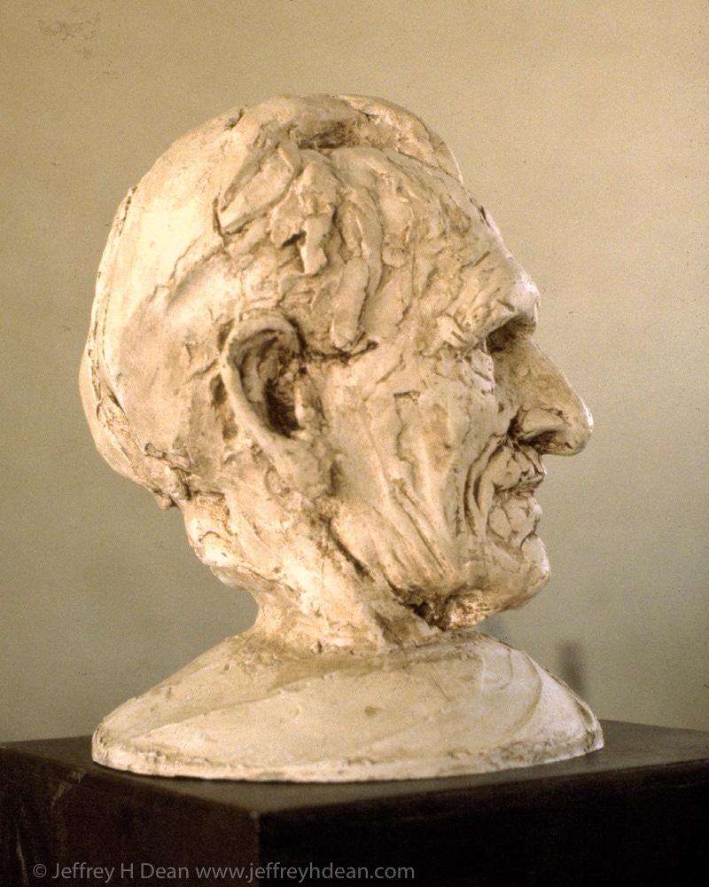 Plaster portrait sculpture of older man.