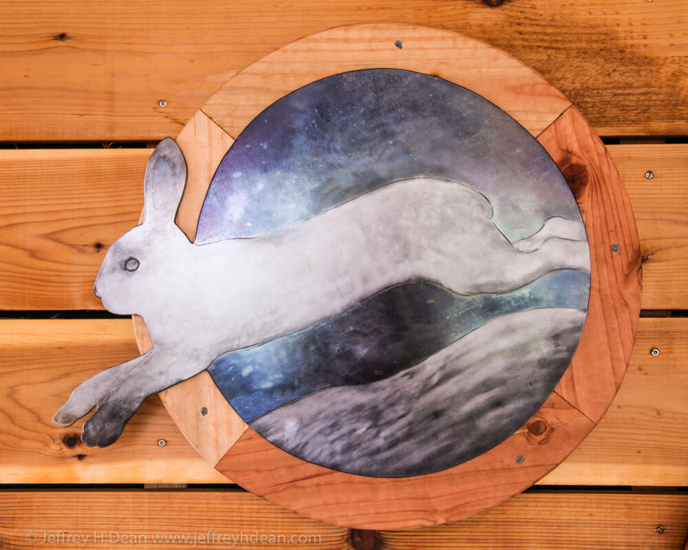 A snowshoe hare darts across the snow in this engraved steel picture.