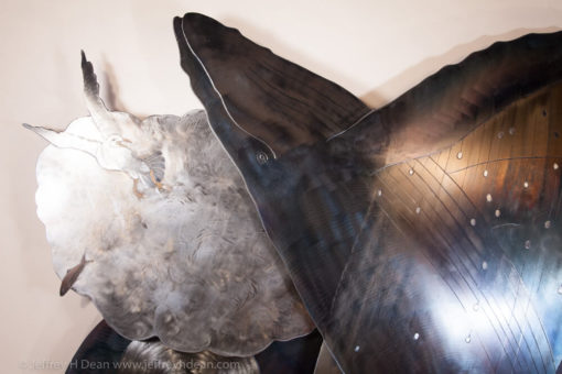 A happily breaching humpback whale interrupts a seagull's evening meal in this layered steel and wood relief.